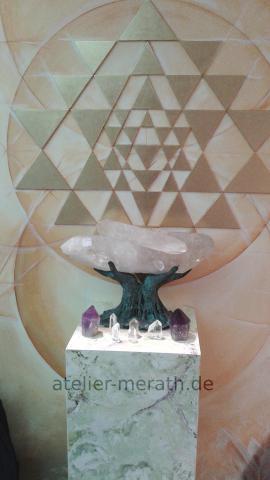 Bronzehand mit Kristall vor Sri Yantra
